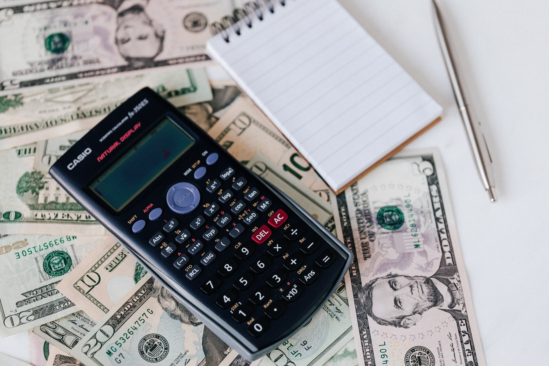 calculator and notepad placed on usa dollars stack